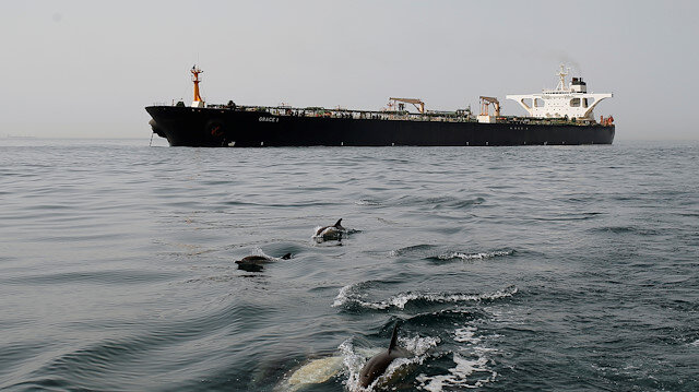Dolphins swim in front of the Iranian oil tanker Grace 1 as it sits anchored after it was seized earlier this month by British Royal Marines off the coast of the British Mediterranean territory on suspicion of violating sanctions against Syria, in the Strait of Gibraltar, southern Spain July 20, 2019. REUTERS/Jon Nazca