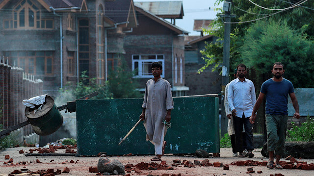 Kashmiris walk past a blockade put up by residents to prevent security personnel from sealing a mosque ground ahead of the Eid-al-Adha prayers during restrictions after the scrapping of the special constitutional status for Kashmir by the Indian government, in Srinagar, August 12, 2019. REUTERS/Danish Siddiqui