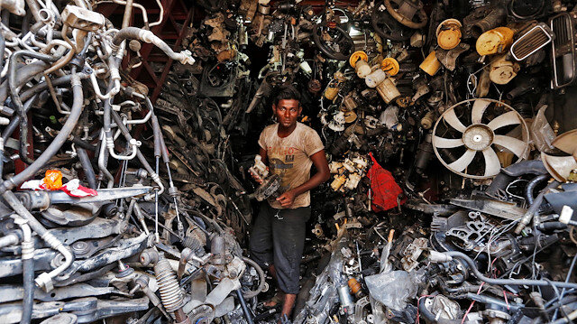 A worker carries a part of a used car inside a shop at a second-hand automobile parts market in Mumbai, India June 1, 2016.