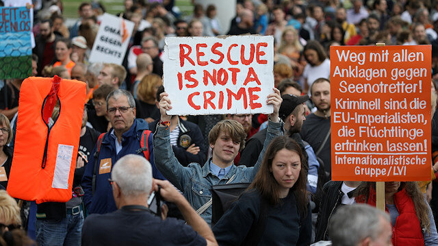 """A man holding a sign that reads """"Rescue is not a Crime"""", attends a demonstration"""