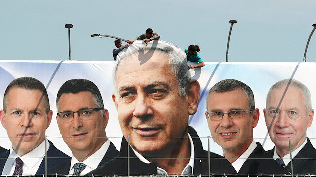 FILE PHOTO: Labourers work on hanging up a Likud election campaign banner depicting Israeli Prime Minister Benjamin Netanyahu with his party candidates, in Jerusalem March 28, 2019. REUTERS/Ammar Awad/File Photo