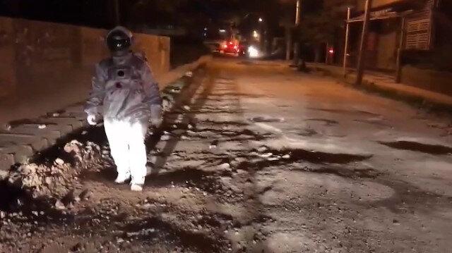 Astronot kıyafeti giyip bozuk yollara dikkat çekti