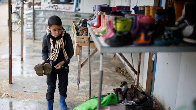A Syrian child buys winter boots during rainy weather at the Al Zaatari refugee camp