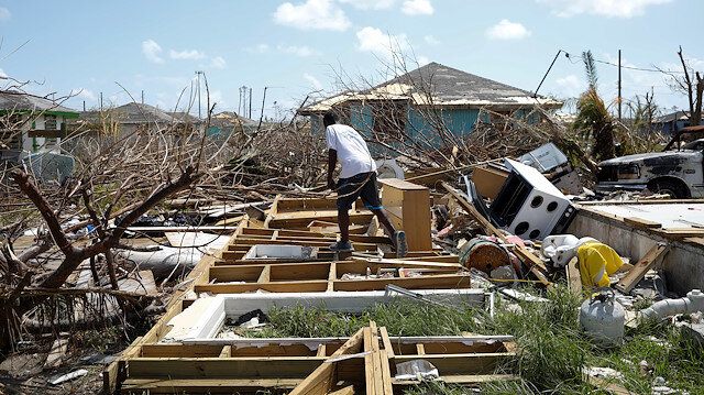 A man walks among the debris of his house after Hurricane Dorian hit the Abaco Islands in Spring City, Bahamas