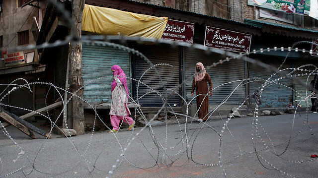 Fil photo: Kashmiri women walk past concertina wire laid across a road during restrictions