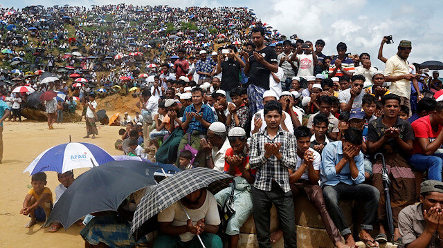 Rohingya refugees take part in a prayer as they gather to mark the second anniversary