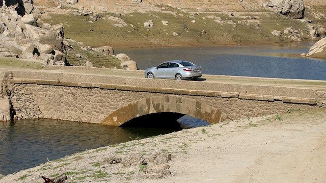 Baraj suyu azalınca su altındaki köprü gün yüzüne çıktı: Görmek için geliyorlar