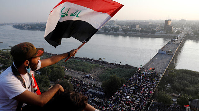 File photo: A demonstrator holds an Iraqi flag as he sits on a building during an anti-government protests in Baghdad, Iraq October 30, 2019