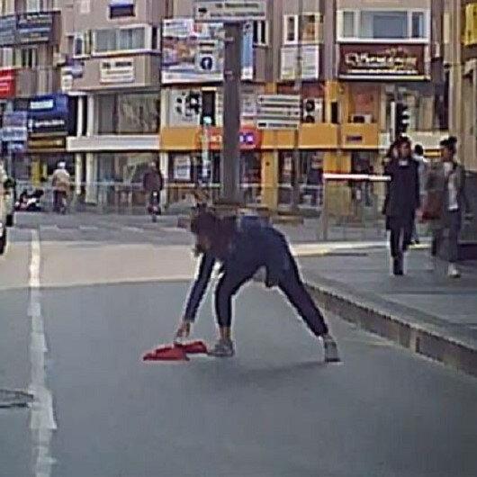Bayrak hassasiyeti duygulandırdı: Yola düşen bayrağı araçlar üstünden geçmesin diye koşup aldı