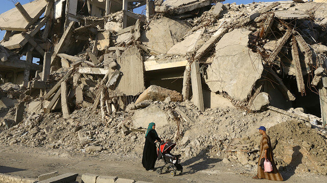 FILE PHOTO: A woman pushes a baby cart as she walks past rubble of damaged buildings in Raqqa, Syria, May 29, 2019. Picture taken May 29, 2019.