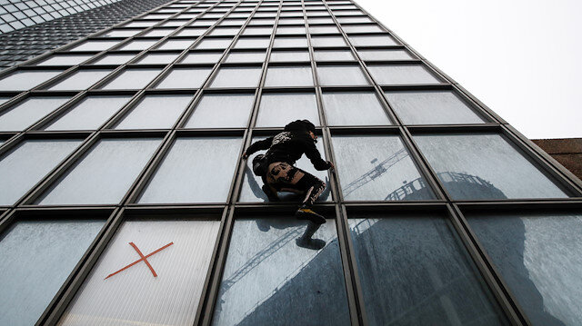 """French climber Alain Robert, also known as """"Spiderman"""", scales the Tour Total skyscraper in support of the anti pensions reform strikers at La Defense financial and business district near Paris, France"""