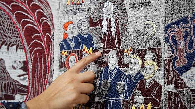 A visitor points at the Starbucks cup of the Game of Thrones Tapestry in Bayeux, France, September 13, 2019. The 87-metre-long tapestry work was made in Northern Ireland to honour the television series Game of Thrones is on display across the street from the better-known original 11th-century Bayeux Tapestry. REUTERS/Charles Platiau