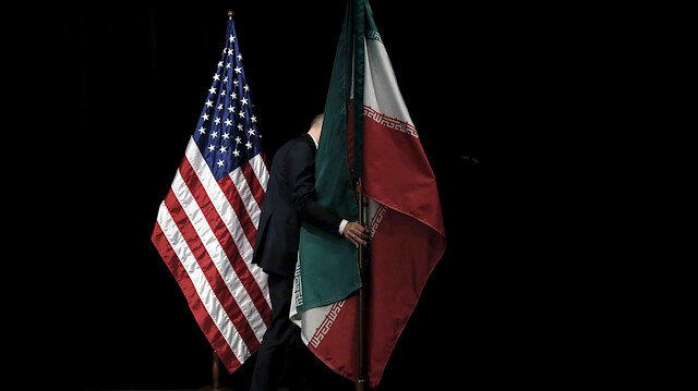 A staff member removes the Iranian flag from the stage after a group picture