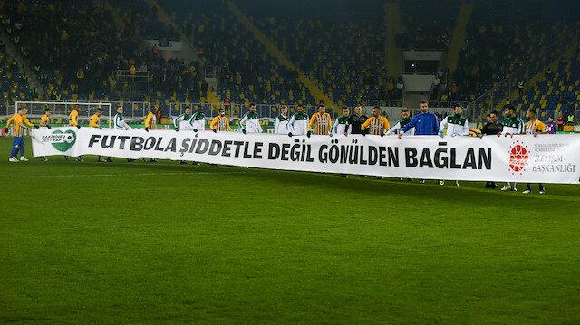 İki takım oyuncuları sahaya 'Futbola şiddetle değil gönülden bağlan' pankartıyla çıktı.