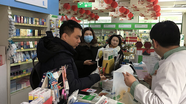 A man pays for masks at a pharmacy in Beijing, China
