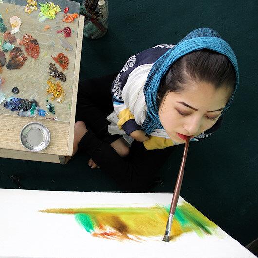 فتاة أفغانية من ذوي الاحتياجات الخاصة تبدع بالرسم بفمها