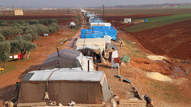 Syrian civilians living at the camp set up on railway