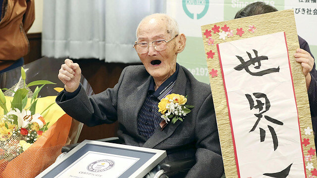 112-year-old Chitetsu Watanabe poses next to the calligraphy reading 'World's Number One' after being awarded as the world's oldest living male by Guinness World Records, in Joetsu, Niigata prefecture, northern Japan February 12, 2020.