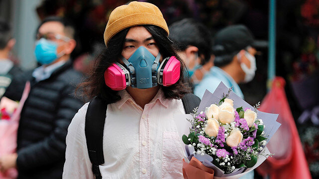 A man wears a gas mask as he holds a bouquet of flowers, following the outbreak of the novel coronavirus on Valentine's Day in Hong Kong, China February 14, 2020. REUTERS/Tyrone Siu
