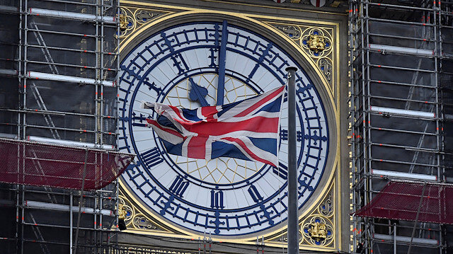 The British union flag is seen fluttering as the clock face of Big Ben shows eleven o'clock