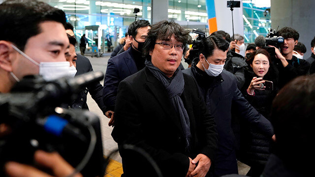 Director of four Oscar award-winning film 'Parasite' Bong Joon-ho is escorted by security personnel as he leaves Incheon International Airport, South Korea, February 16, 2020. REUTERS/Kim Hong-Ji