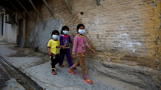 Iraqi children wear protective masks as they walk near a religious school