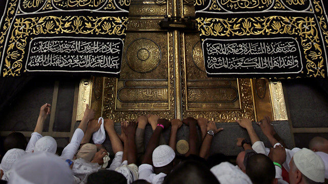 Muslims touch and pray at the door of the Kaaba and touch and kiss the al-Hajr al-Aswad