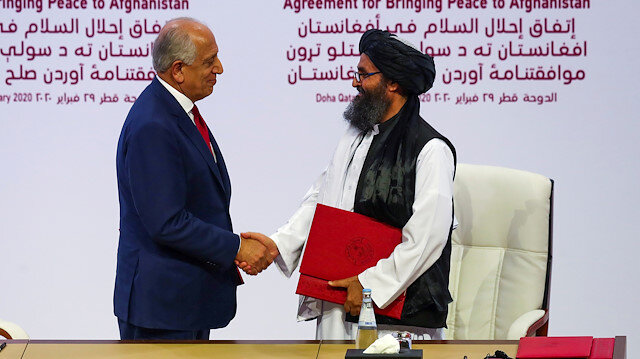 FILE PHOTO: Mullah Abdul Ghani Baradar, the leader of the Taliban delegation, and Zalmay Khalilzad, U.S. envoy for peace in Afghanistan, shake hands after signing an agreement at a ceremony between members of Afghanistan's Taliban and the U.S. in Doha, Qatar, February 29, 2020
