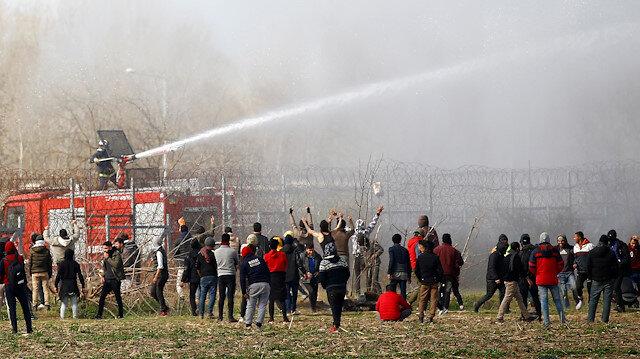 A Greek fire fighter uses a water cannon as migrants gather on the Turkish-Greek border near Turkey's Pazarkule border crossing with Greece's Kastanies, in Edirne, Turkey March 7, 2020.