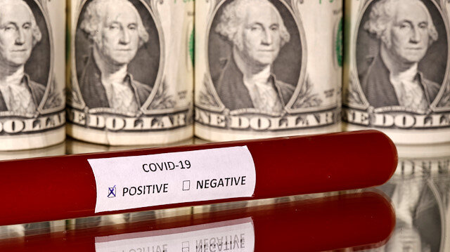 FILE PHOTO: A test tube labelled with the coronavirus is seen in front of U.S. dollar banknotes, in this illustration taken on March 1, 2020