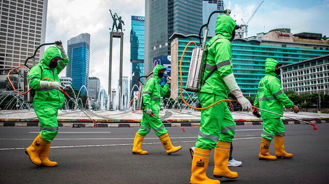 File photo: Workers walk in protective suits during an operation of spraying disinfectant to prevent the spread of coronavirus disease (COVID-19) in Jakarta, Indonesia March 22, 2020 in this photo taken by Antara Foto