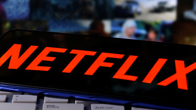 """A smartphone with the Netflix logo is seen on a keyboard in front of displayed """"Streaming service"""" words in this illustration taken March 24, 2020. REUTERS/Dado Ruvic"""