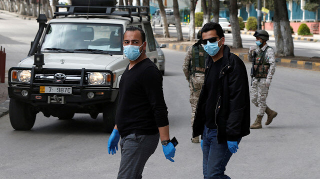 People wear face masks at a check point in the northern governorate of Irbid