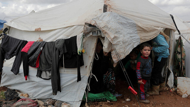 An internally displaced Syrian child from Idlib, stands outside a tent in Azaz
