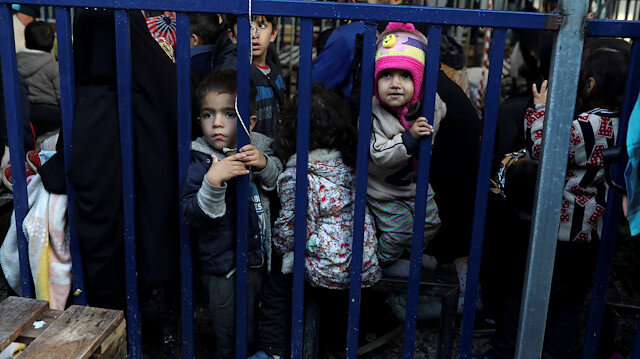 Children stand next to a metal barrier as newly-arrived refugees and migrants wait to be registered at the Moria camp, on the island of Lesbos, Greece, November 27, 2019.