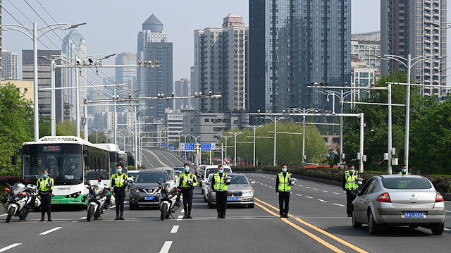 Traffic police officers and vehicle drivers observe a moment of silence on a road in Wuhan, Hubei province, as China holds a national mourning for those who died of the coronavirus disease (COVID-19), on the Qingming tomb-sweeping festival, April 4, 2020