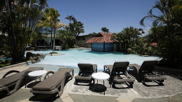 Empty sunbathing chairs are seen near a pool in a hotel in Costa Rica