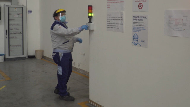 A worker is seen by a traffic light limiting the access to bathrooms inside the ISA factory that has introduced new safety measures to respect social distancing among workers to stop the spread of the coronavirus disease (COVID-19) in Bastia Umbra, Italy, April 22, 2020, in this still image taken from video. REUTERS TV via REUTERS