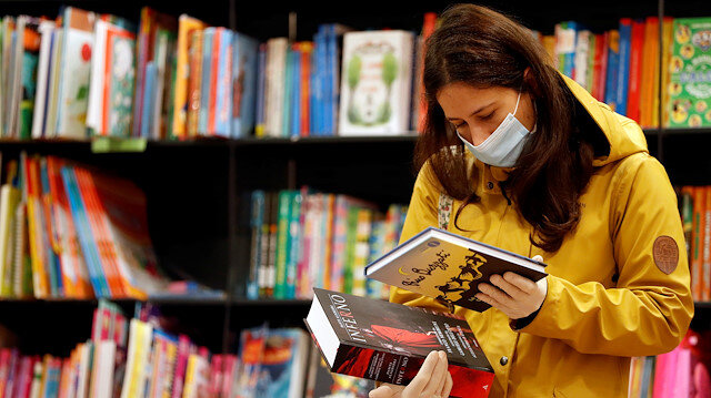A customer wearing a protective face mask and gloves checks books at a newly opened bookstore, as only very few restrictions are relieved under the coronavirus disease (COVID-19) lockdown rules, in Rome, Italy April 20, 2020. REUTERS/Yara Nardi