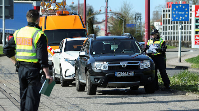 FILE PHOTO: A German police officer checks a car at the border with France due to the spreading of the coronavirus disease (COVID-19) in Saarbruecken, Germany, March 16, 2020.
