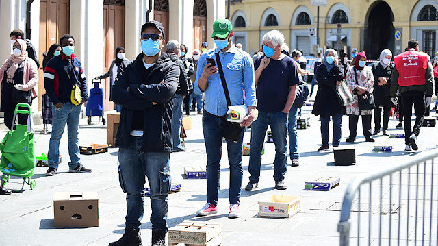 People wearing protective face masks queue at Porta Palazzo market in Turin after it reopened with social distancing rules as Italy begins a staged end to a nationwide lockdown, following the outbreak of the coronavirus disease (COVID-19), Turin, Italy, May 4, 2020.
