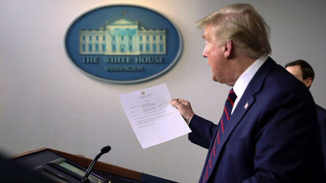 U.S. President Donald Trump holds a letter from White House physician Commander Sean Conley that reports that the president has tested negative a second time for coronavirus disease during a use of the new 15-minute result test at the White House in Washington, U.S., April 2, 2020. REUTERS/Tom Brenner