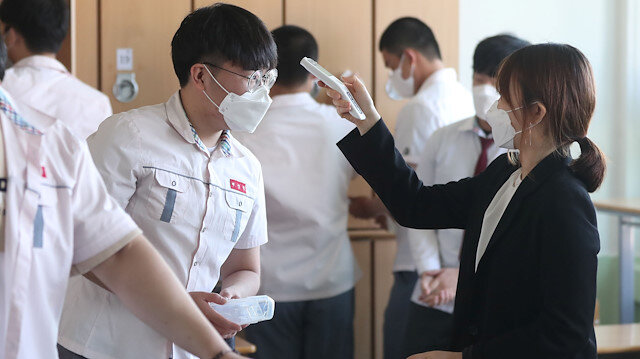 A high school teacher checks body temperature of a student at a classroom following the global outbreak of the coronavirus disease (COVID-19), in Gimhae, South Korea, May 20, 2020. Yonhap/via REUTERS ATTENTION EDITORS - THIS IMAGE HAS BEEN SUPPLIED BY A THIRD PARTY. NO RESALES. NO ARCHIVE. SOUTH KOREA OUT. NO COMMERCIAL OR EDITORIAL SALES IN SOUTH KOREA.