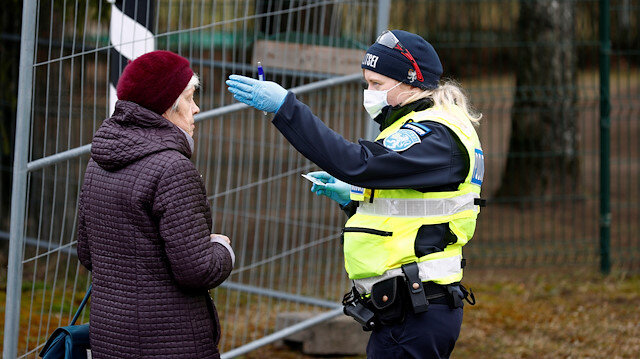 File photo: An Estonian police officer stops a woman at border crossing point as Estonia reintroduces border control and a ban to enter Estonia for foreigners as a preventive measure against the coronavirus disease (COVID-19) in Valga, Estonia March 17, 2020