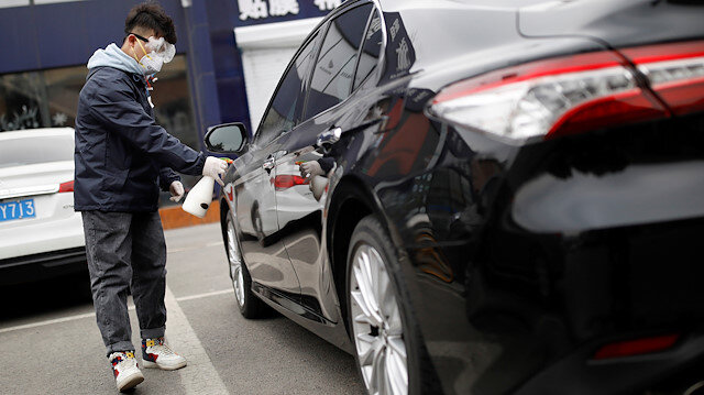 FILE PHOTO: A staff member disinfects a vehicle at a service centre of car-hailing service Didi Chuxing, as the country is hit by an outbreak of the new coronavirus, in Beijing, China February 27, 2020