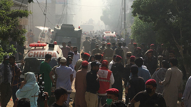 Ambulances and fire brigade vehicles gather at the site of a passenger plane crash in a residential area near an airport in Karachi, Pakistan May 22, 2020.