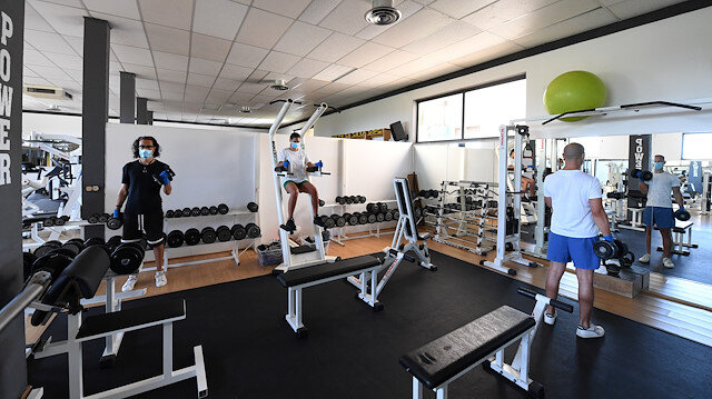 Gym-goers wearing protective face masks and gloves exercise as the gym reopens