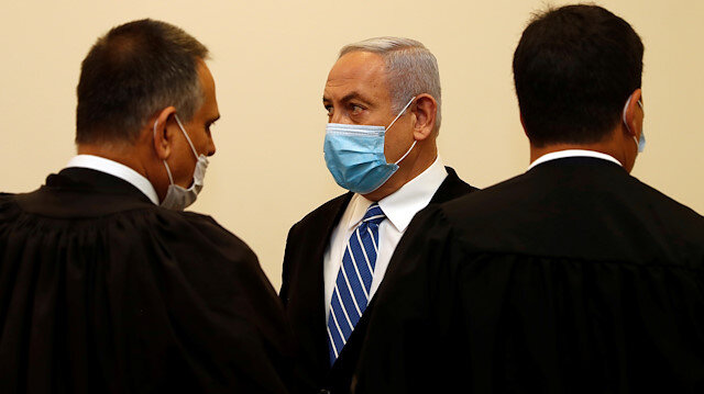 Israeli Prime Minister Benjamin Netanyahu, wearing a face mask, stands inside the court room as his corruption trial opens at the Jerusalem