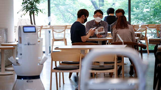 Customers wait at a cafe where a robot that takes orders, makes coffee and brings the drinks straight to customers is being used in Daejeon, South Korea, May 25, 2020