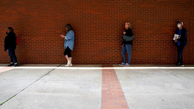 People who lost their jobs wait in line to file for unemployment benefits